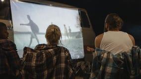 Przyjaciele ogląda film na ekranie w campsite zdjęcie royalty free