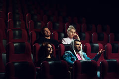 Przyjaciele ogląda film w kinowym teatrze zdjęcia stock
