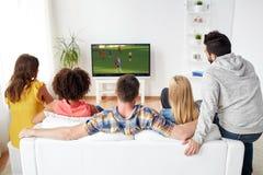 Przyjaciele ogląda mecz piłkarskiego na tv w domu Obrazy Stock