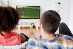 Przyjaciele ogląda mecz piłkarskiego na tv w domu Obraz Stock