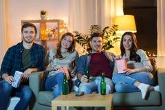 Przyjaciele ogl?da tv w domu z piwem i popkornem zdjęcia royalty free