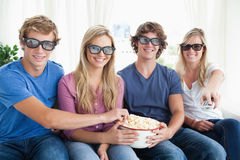Przyjaciele ono uśmiecha się gdy jedzą popkorn i oglądają 3d film Fotografia Stock
