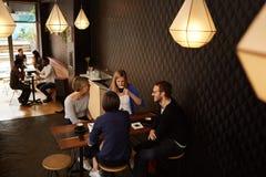 Przyjaciele opowiada podczas gdy cieszący się świeżą kawę w kawiarni wpólnie Zdjęcie Royalty Free