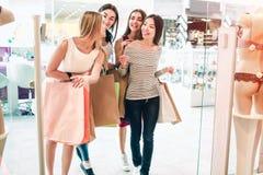 Przyjaciele opowiadają wśród one i chodzą w bielizna sklep Trzymają torbę Dziewczyny robią zakupy i zdjęcia stock