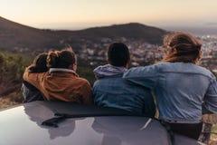 Przyjaciele patrzeje miasto od drogi na górze wzgórza obraz stock