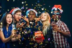 Przyjaciele przy nowego roku ` s przyjęciem, jest ubranym Santa kapelusze, tana i podmuchowych confetti, obraz royalty free