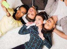 Przyjaciele relaksuje na dywanie z gadżetami Fotografia Royalty Free