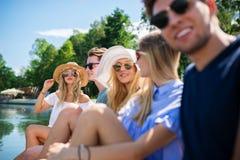 Przyjaciele relaksuje przy jeziorem Zdjęcia Stock