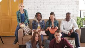 Przyjaciele siedzą w żywym pokoju i bawić się gemową konsolę zdjęcie wideo