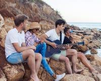 Przyjaciele siedzi na kamieniach na plaży Mężczyzna bawić się gitarę Fotografia Royalty Free