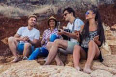 Przyjaciele siedzi na kamieniach na plaży Mężczyzna bawić się gitarę Zdjęcia Stock