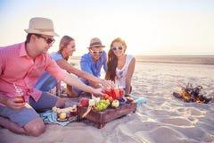 Przyjaciele siedzi na piasku przy plażą w okręgu Obrazy Stock