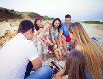 Przyjaciele siedzi na piasku przy plażą w okręgu z marshmal Zdjęcie Stock