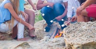 Przyjaciele siedzi na piasku przy plażą w okręgu z marshmal Zdjęcia Royalty Free