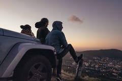 Przyjaciele siedzi na szczycie patrzeje miasto below fotografia royalty free