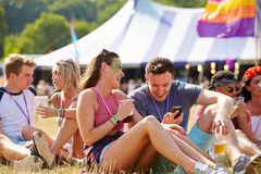 Przyjaciele siedzi na trawie używać smartphone przy festiwalem muzyki Fotografia Stock