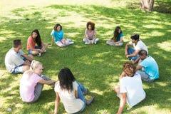 Przyjaciele siedzi w okręgu przy parkiem Obrazy Stock