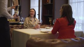 Przyjaciele siedzi w restauracyjnym, czekać na rozkaz i kelnerów szkła z czerwonym winem, przybycia i pełnych zdjęcie wideo