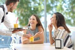 Przyjaciele spotyka w barze z kelner porcją Obraz Royalty Free