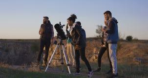 Przyjaciele stargazing wpólnie używać fachowego teleskop zdjęcie wideo
