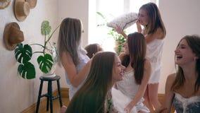 Przyjaciele synchronizują, szczęśliwe dziewczyny w piżamach cieszą się grę z poduszkami na łóżku przy sen przyjęciem zbiory