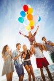 Przyjaciele tanczy na piasku z balonem Obrazy Royalty Free