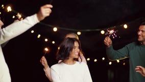 Przyjaciele tanczy przy dachu przyjęciem z sparklers zbiory