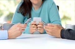 przyjaciele używa ich smartphones przy barem zdjęcia stock