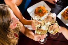 Przyjaciele w clink bardzo dobrych restauracyjnych szkłach Zdjęcia Royalty Free