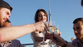 Przyjaciele wznosi toast napoje i ma podczas przyjęcia na jachcie zbiory