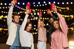 Przyjaciele wznosi toast partyjne filiżanki na dachu przy nocą obraz royalty free