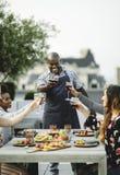 Przyjaciele wznosi toast z szefem kuchni przy latem bawją się obraz stock