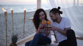Przyjaciele z koktajlem na zwrotnikach wyrzucać na brzeg, kochająca para ma koktajl w rękach, mężczyzna i kobiety mieszać piją, m zdjęcie wideo