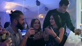 Przyjaciele z kolorowymi koktajlami robią grzance blisko zakazują kontuar w klubie na przyjęciu zbiory wideo