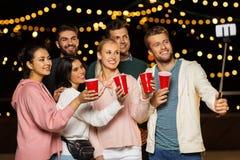 Przyjaciele z napojami bierze selfie przy dachu przyjęciem obraz royalty free
