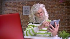 Przyjemna caucasian babcia używa jego pastylkę w krześle podczas gdy siedzący blisko czerwonego komputeru z falistym białym włosy