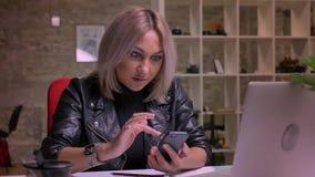 Przyjemna caucasian blondynki kobieta swiping jej smartphone podczas gdy siedzieć odizolowywam w lekkim nowożytnym ceglanym domu