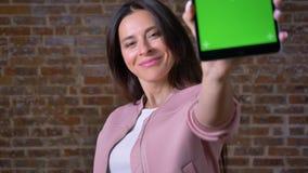 Przyjemna caucasian brunetki dziewczyna z dumnym ufnym pojawienie seansu zieleni ekranem na pastylce przy kamerą prosto