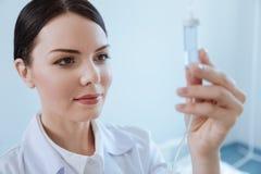 Przyjemna fachowa pielęgniarka patrzeje IV kapinosa butelkę zdjęcie royalty free
