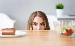 Przyjemna podstępna kobieta wybiera co jeść obrazy stock