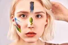 Przyjemna przyglądająca kobieta z pięknym sztuki makeup na twarzy, krótkiego blondynka włosy, pozy przeciw białemu pracownianemu  fotografia royalty free