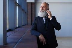 Przyjemna samiec opowiada na telefonie z popielatą brodą podczas gdy opierający dalej Fotografia Stock