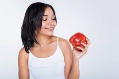 Przyjemna uśmiechnięta kobieta patrzeje czerwonego dzwonkowego pieprzu Zdjęcia Royalty Free