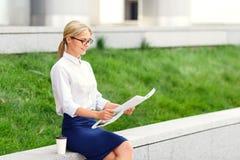 Przyjemnej kobiety czytelnicza gazeta zdjęcie royalty free