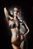 przyjemność Glansowana kobieta z Złotą ciało sztuką glamorize Na tle szarości ściana fotografia royalty free