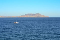 Przyjemności łódź unosi się na tle góry i bezchmurny niebo Zdjęcia Royalty Free