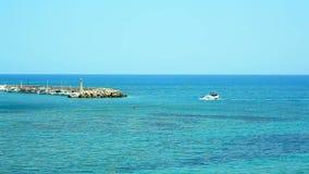 Przyjemności łódź unosi się w błękitnym morzu piękna wyspa z latarnią morską pojęcie cudowny wakacje w Grecja zbiory