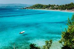 Przyjemności biała łódź w krysztale - jasna błękitna woda morska Spektakularny Platis Gialos i Makris Gialos plaża, Kefalonia wys zdjęcia stock