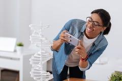 Przyjemny ładny uczeń bierze fotografię DNA model Obraz Stock