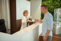 Przyjemny administrator daje klientowi filiżance herbata obraz royalty free